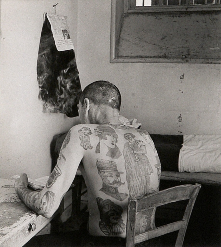 robert doisneau - A man from behind with big tattoos